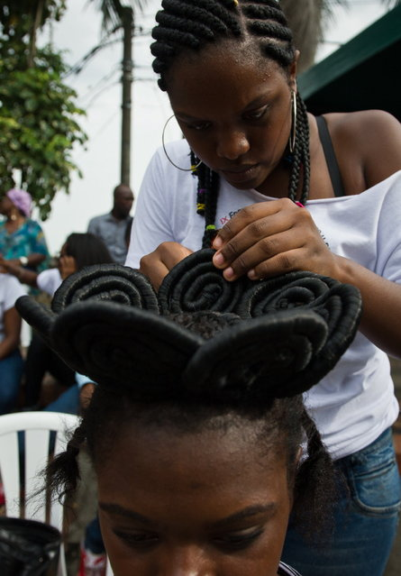 A woman gets an Afro-Colombian hairstyle during the 9th contest of Afro-hairdressers, in Cali, Valle del Cauca departament, Colombia, on May 12, 2013. The Afro hairstyles have their origins in the time of slavery, when women sat to comb their children hair after work. (Photo by Luis Robayo/AFP Photo)