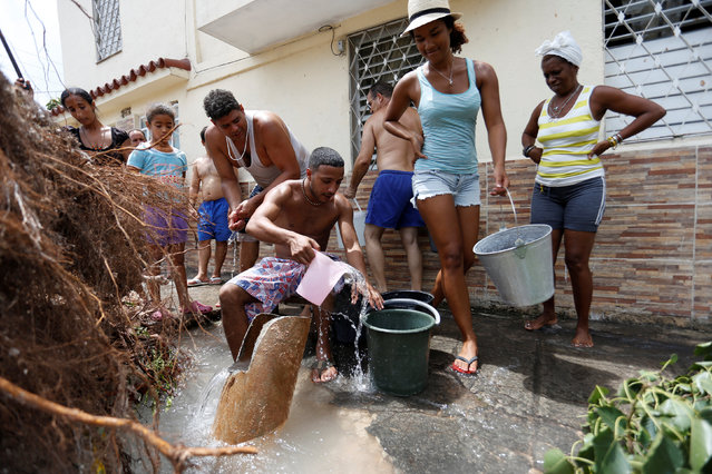 People collect water from a broken tube after Hurricane Irma caused flooding and a blackout in Havana, Cuba, September 11, 2017. (Photo by Reuters/Stringer)