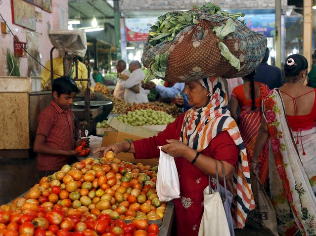 A woman carrying cabbage leaves on her head buys tomato at a market in Ahmedabad, India, November 9, 2015. (Photo by Amit Dave/Reuters)
