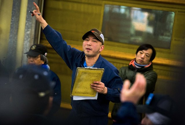 An auctioneer gestures as wholesalers bid for frozen tuna during the New Year's auction at the Tsukiji fish market in Tokyo January 5, 2015. (Photo by Thomas Peter/Reuters)