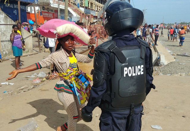 A police officer chases shoppers to clear the streets of the Red Light market on the first day of lockdown to stop the spread of the coronavirus disease (COVID-19) in Monrovia, Liberia on April 11, 2020. (Photo by Derick Snyder/Reuters)