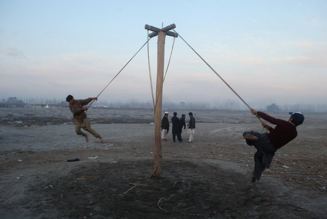 Boys play on a swing at a slum on the outskirts of Peshawar December 31, 2014. (Photo by Khuram Parvez/Reuters)
