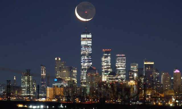 A crescent moon rises before sunrise above lower Manhattan and One World Trade Center in New York City on January 10, 2021 as seen from Kearny, New Jersey. (Photo by Gary Hershorn/Getty Images)