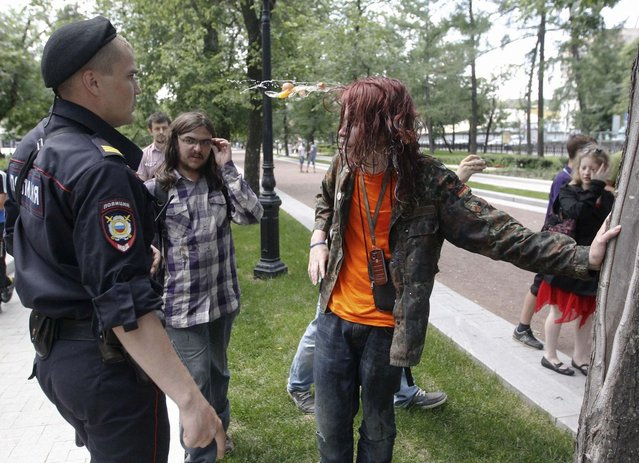 """A gay rights activist is hit by an egg during a protest against a proposed new law termed by the State Duma, the lower house of Parliament, as """"against advocating the rejection of traditional family values"""" in central Moscow June 11, 2013. Activists say the bill, backed by Russian President Vladimir Putin's allies in parliament, would prohibit all gay-rights rallies and fear it is fuelling violence against gays. Russian authorities say two recent murders were motivated by homophobia. (Photo by Maxim Shemetov/Reuters)"""