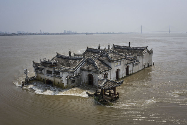 An aerial view of the Kwanyin Temple in the middle of the flooded Yangtze River on July 24, 2020, in Ezhou, China. The temple, on a rocky island in the mighty river, was first built in 1345, and has collapsed and been rebuilt multiple times across history. (Photo by Getty Images/China Stringer Network)