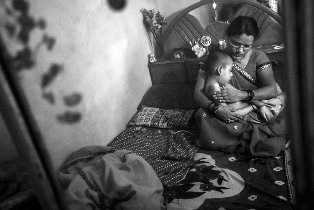 Rishikesh, 8 years old, with his mother Sangeeta at home in the Pushpa Nagar neighborhood. Rishikesh was born to parents contaminated by a carcinogenic and mutagenic water supply. (Photo by Giles Clarke/Getty Images)