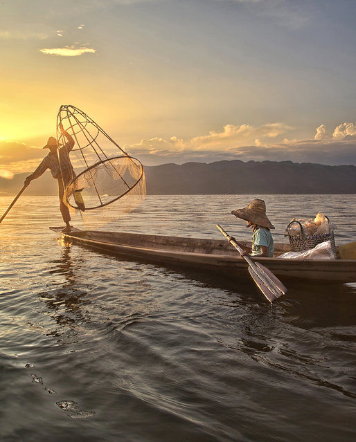 """Fishing"". A father and daughter with a fish in the net at sunset on Inle Lake, Myanmar. (Photo and caption by Cynthia MacDonald/National Geographic Traveler Photo Contest)"