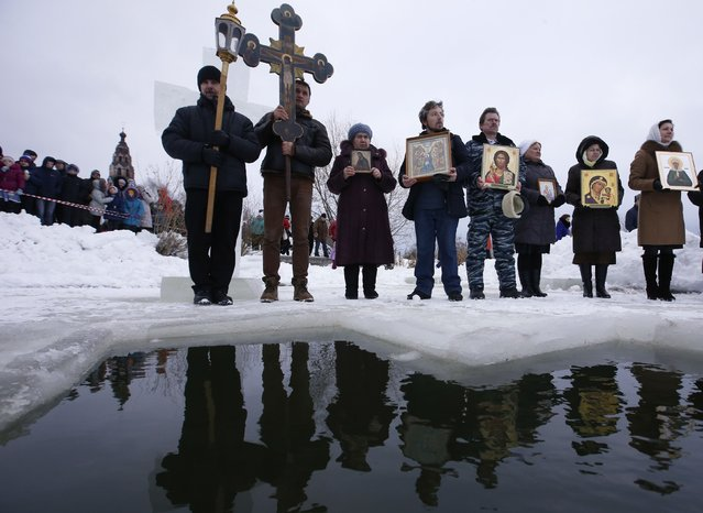 People attend an Orthodox religious service during a water blessing ceremony on Epiphany Day in the village of Velikoye, Yaroslavl region, January 18, 2015. (Photo by Sergei Karpukhin/Reuters)