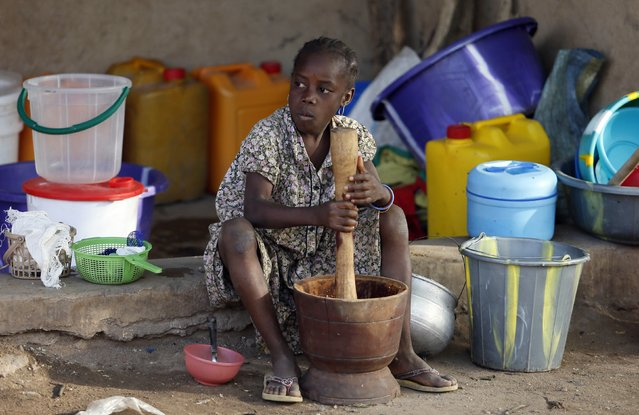 A girl displaced as a result of Boko Haram attacks in the northeast region of Nigeria, uses a mortar and pestle at a camp for internally displaced people in Yola, Adamawa State January 14, 2015. (Photo by Afolabi Sotunde/Reuters)