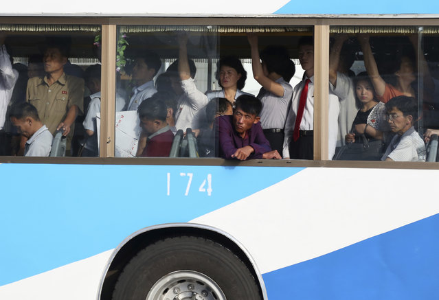 People pack a trolley bus during morning rush hour in Pyongyang, North Korea, Tuesday, June 19, 2018. The city trolley is one of the more common forms of public transportation among North Koreans living in the capital city. (Photo by Dita Alangkara/AP Photo)