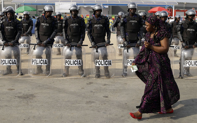 A woman walks past police officers outside the stadium during the African Cup of Nations Group B soccer match between Tunisia and Zambia in Ebibeyin, Equatorial Guinea, Thursday, January 22, 2015. (Photo by Themba Hadebe/AP Photo)