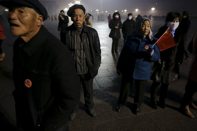 "People gather before dawn at the Tiananmen Square for a flag-raising ceremony amid heavy smog, after the city issued its first ever ""red alert"" for air pollution, in Beijing December 9, 2015. (Photo by Damir Sagolj/Reuters)"