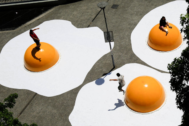 "People are seen on giant fried eggs art installation as part of ""Hecho en Casa"" (Made at home) urban artwork festival in downtown Santiago, Chile, November 8, 2016. (Photo by Pablo Sanhueza/Reuters)"