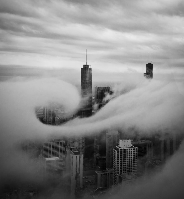 """Swirl"". This was taken on 95th floor of John Hancock Building. I was fortunate to watch fast moving low hanging clouds swept through the city buildings during late afternoon. A cloud swirled around the Trump Tower for a very brief moment for me to capture two frames. This is one of the two. Location: John Hancock Building Chicago IL USA. (Photo and caption by Jian Lou/National Geographic Traveler Photo Contest)"