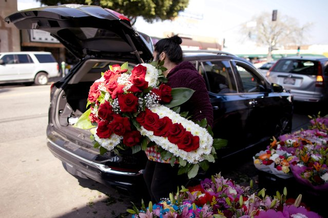 A woman lifts a funeral display into a car in the flower district as the coronavirus disease (COVID-19) outbreak continues, ahead of Valentine's Day in Los Angeles, California, U.S., February 4, 2021. (Photo by Lucy Nicholson/Reuters)
