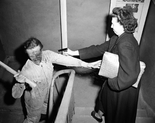 """This """"robber"""" who tried to snatch the lady's handbag on a lone stairway is disabled by a pistol shot of colored lye, April 3, 1950. The new shock weapon is on sale in Germany, where civilians are not allowed to carry fire arms. (Photo by Hanns J. Jaeger/AP Photo)"""