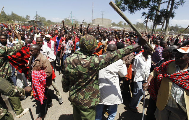 A policeman attempts to block residents chanting slogans during protests to oust the Narok county Governor Samuel Tunai in Narok, Kenya, January 26, 2015. (Photo by Thomas Mukoya/Reuters)