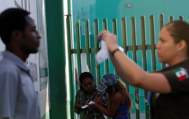 An immigration officer takes a picture of a migrant as others fill a form outside the immigration office to fix their papers and continue their journey in Tapachula, Chiapas, Mexico November 16, 2016. (Photo by Carlos Jasso/Reuters)