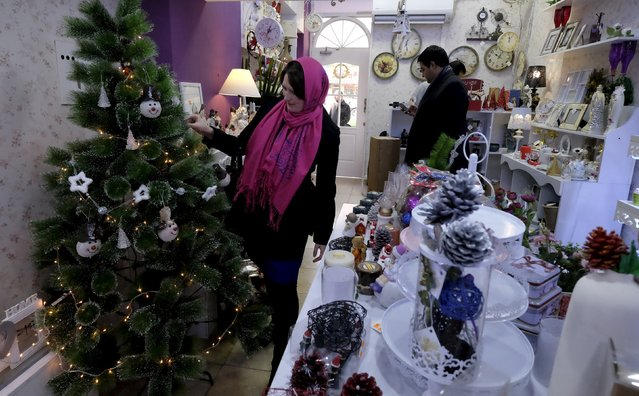 An Iranian Christian woman looks at a Christmas tree at a shop in central Tehran December 23, 2015. (Photo by Raheb Homavandi/Reuters)