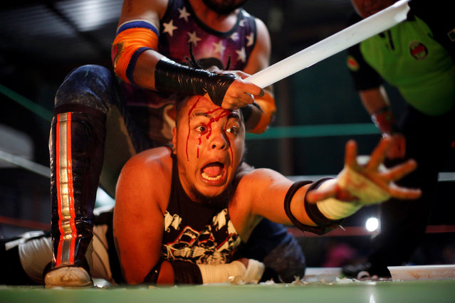 Wrestler known as Gio Malkriado (top) fights with a fluorescent tube with wrestler Ciclope during an extreme wrestling fight at a temporary wrestling ring inside a car wash in Tulancingo Hidalgo, Mexico October 8, 2016. When the time comes for the so-called Extreme Star Fight, six wrestlers climb into the ring. Once the fighting begins, anything goes. They bash each other with chairs and long neon lights, causing small explosions and scattering tiny pieces of glass everywhere. The fighters, about half of whom wear masks, even use plastic knives and forks to hurt their opponents. Quickly, blood begins to stain the faces of the combatants and the crowd goes wild, shouting even louder. The screaming and yelling goes on for some time as fans swear at the fighters who ignore them. (Photo by Carlos Jasso/Reuters)