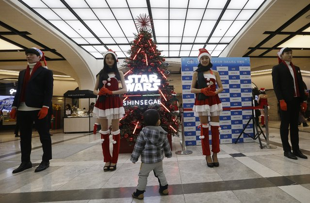 A child watches models wearing Santa Claus costumes as they attend a special event to promote business in coincide with Christmas at Shinsegae department store in Seoul, South Korea, Thursday, December 24, 2015. A lot of South Korean companies take advantage of the Christmas season to promote their business amid weak sales and economic slowdown. (Photo by Ahn Young-joon/AP Photo)