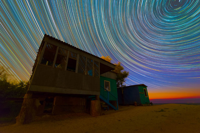 These are the spectacular snaps of swirling star trails which transform the night sky into a kaleidoscope of color. Keen photographer Evgeniy Zaytsev, 24, captured the stunning shots on trips to Crimea, Altai and Murom, Russia. The pictures of circular star trails are formed by merging multiple photos taken over the course of several hours. Here: vibrate, colorful star trails over an abandoned beach house. (Photo by Evgeniy Zaytsev/Caters News)