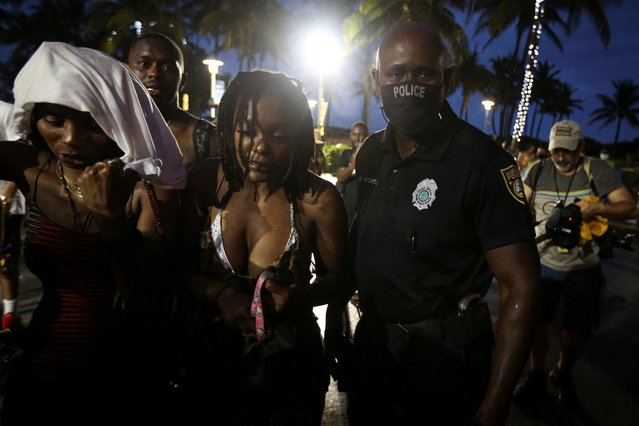 A Miami Beach police officer enforces an 8pm curfew imposed by local authorities on spring break festivities, amid the coronavirus disease (COVID-19) pandemic, in Miami Beach, Florida, U.S., March 27, 2021. (Photo by Marco Bello/Reuters)