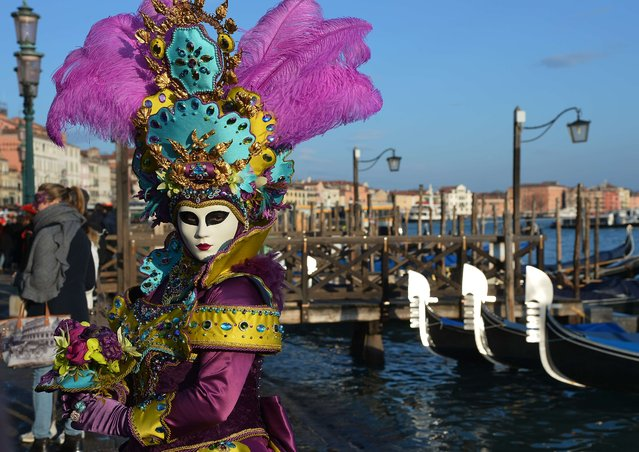"""A costumed reveller poses near gondolas during the carnival on February 7, 2015 in Venice. The 2015 edition of the Venice carnival is untitled """"The world's most delicious festival"""" and runs till February 17th. (Photo by Vincenzo Pinto/AFP Photo)"""