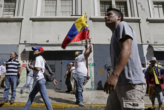 A supporter of Venezuela's opposition holds a national flag some streets away from the building housing the National Assembly in Caracas, January 5, 2016. (Photo by Marco Bello/Reuters)