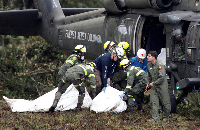 A Colombian air force helicopter retrieves the bodies of victims from the wreckage of a plane that crashed into the Colombian jungle with Brazilian soccer team Chapecoense onboard near Medellin, Colombia, November 29, 2016. (Photo by Jaime Saldarriaga/Reuters)