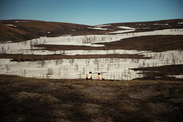 April 2012. Two young men sit on a hillock overlooking a landscape still partially covered in snow. After spending nine months in confined spaces, Norilsk inhabitants like to escape to the tundra when the weather turns nice. (Photo by Elena Chernyshova)