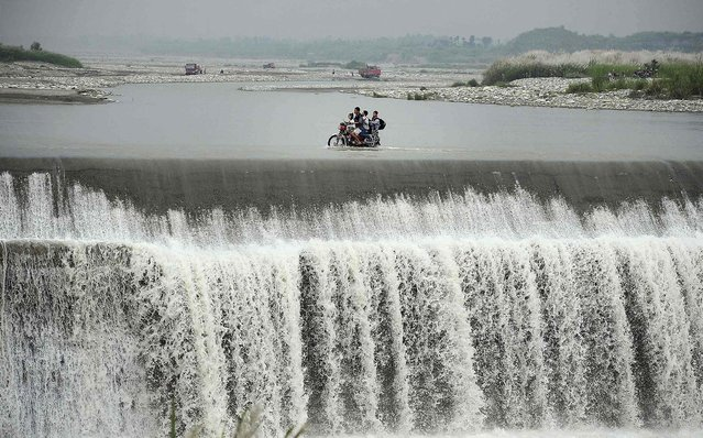 A man rides a motorcycle carrying his children along the top of a dam which is flooded by an overflowing river near Junyue township of Pengzhou, China, on September 15, 2013. Residents have been crossing the river along the top of the dam to save on travel time, after fresh floods crushed a bridge near the dam in July. (Photo by Reuters)