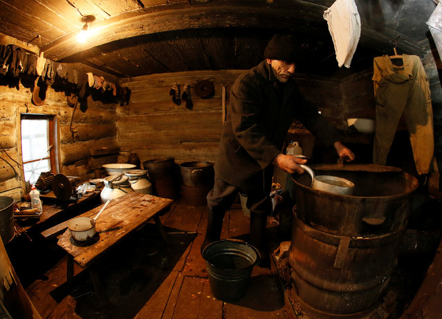 Mikhail Baburin, 66, fills a bucket with hot water from a barrel at a bath room of his house in the remote Siberian village of Mikhailovka, Krasnoyarsk region, Russia, December 5, 2016. (Photo by Ilya Naymushin/Reuters)