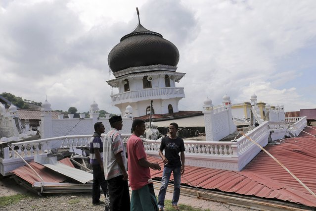 Men inspect a collapsed mosque after an earthquake in Pidie Jaya, Aceh province, Indonesia, Wednesday, December 7, 2016. A strong undersea earthquake rocked Indonesia's Aceh province early on Wednesday, killing a number of people and causing dozens of buildings to collapse. (Photo by Heri Juanda/AP Photo)