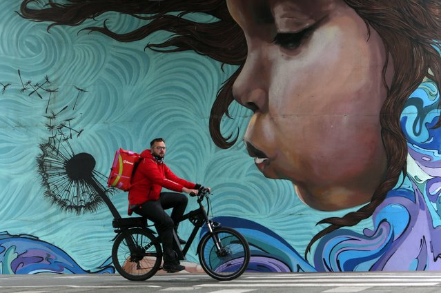 """A man rides a bicycle by a graffiti under the """"Old Sava bridge"""" over Sava river in Belgrade, Serbia, Wednesday, May 19, 2021. (Photo by Darko Vojinovic/AP Photo)"""