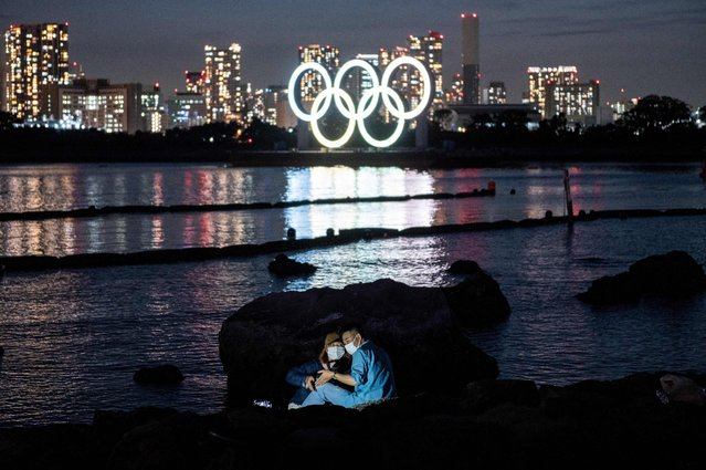 A couple pose for pictures before the lit Olympic rings at the Odaiba waterfront in Tokyo on May 6, 2021. (Photo by Philip Fong/AFP Photo)