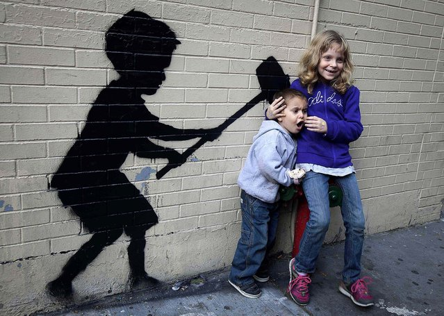 Children pose for their parent's photo with an installation of Banksy's art on October 20, 2013. (Photo by Carlo Allegri/Reuters)