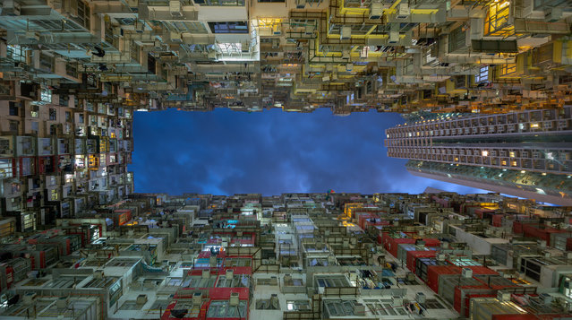 "Winner. ""I took this vertical image in the Quarry Bay district of Hong Kong during the dusk 'blue hour', when there was a perfect balance between the ambient light in the sky and the artificial lights of the high-rise residential buildings"". MICK RYAN, JUDGE: ""Quarry Bay is a rich area for great shots and this is a particularly striking image of these old apartments, a unique perspective that was wisely taken as the light fades and the apartment lights come on"". (Photo by Jatinder Heer/The Guardian)"
