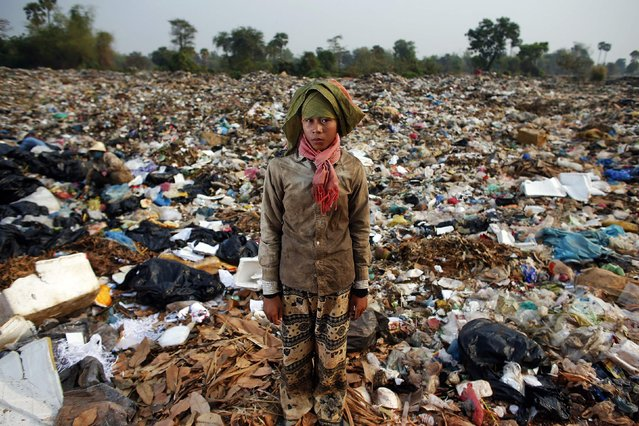 Chan Thy, a 15-year-old girl, poses for a picture while collecting usable items at landfill dumpsite outside Siem Reap March 19, 2015. She works non-stop at the dumpsite earning 2 USD a day after finishing six-grade primary school two years ago. (Photo by Athit Perawongmetha/Reuters)