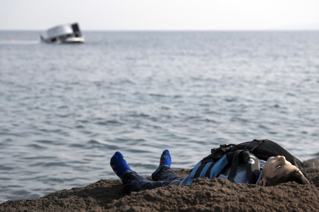 The dead body of a migrant boy lies on the beach near the Aegean town of Ayvacik, Canakkale, Turkey, Saturday, January 30, 2016. (Photo by Halit Onur Sandal/AP Photo)