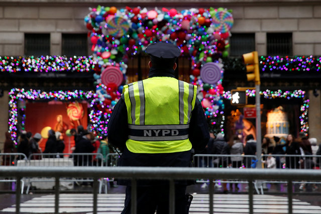 A member of the New York Police Department stands watch outside Saks Fifth Avenue on Christmas Eve in Manhattan, New York City, U.S., December 24, 2016. (Photo by Andrew Kelly/Reuters)
