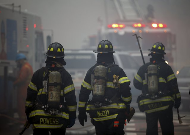 New York City Fire Department firefighters walk towards the site of where a residential apartment building collapsed and was engulfed in flames in New York City's East Village neighborhood March 26, 2015. (Photo by Mike Segar/Reuters)