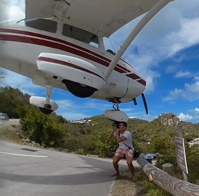 As the light aircraft came in to the Gustaf III Airport in St Barts, one photographer tried to capture an once-in-a-lifetime image. (Photo by Sébastien Politano/Caters News)