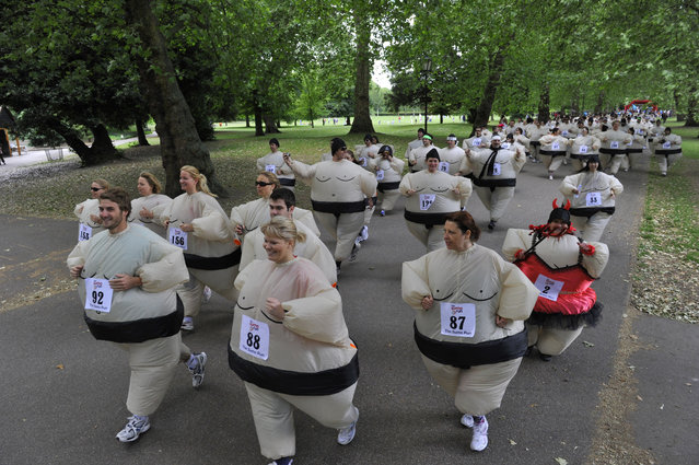 Runners dressed in inflatable Sumo costumes take part in a charity 5km (3 miles) run at Battersea Park in London June 19, 2010. Organisers claimed a new world record for a mass Sumo suit gathering at the annual event. (Photo by Toby Melville/Reuters)