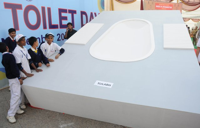 School children pose with the giant toilet pot replica to mark World Toilet Day in New Delhi, India, 19 November 2013. The event was organized by the Sulabh international a non government organization aimed to educate people about the health and social aspects of sanitation. (Photo by EPA/STR)