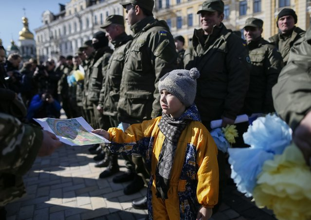 """A boy presents his painting to serviceman of the Ukrainian national guard battalion """"Donbass"""" before they depart to the frontlines in eastern Ukraine, in central Kiev, March 17, 2015. (Photo by Gleb Garanich/Reuters)"""
