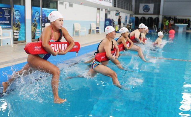 Lifeguards from a branch of the National Red Cross enter a pool to rescue a simulated drowning swimmer in Suwon, south of Seoul, South Korea, 15 June 2021, as they take part in a rescue drill to get ready for the summer season. (Photo by Yonhap/EPA/EFE)