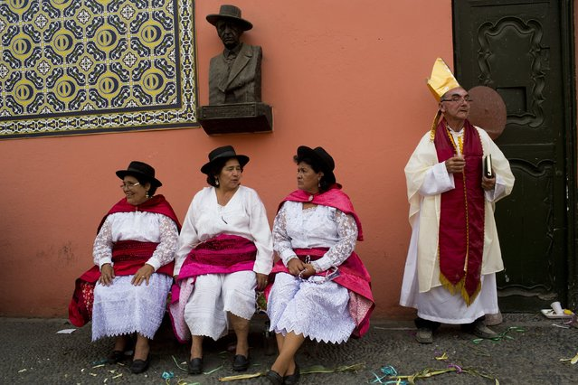 In this Sunday, March 29, 2015 photo, three women await their group's turn to perform in the Vencedores de Ayacucho dance festival, in the Acho bullring in Lima, Peru, while a man dressed as a bishop rests after performing with his dance troupe. In Sunday's dances, people of all ages, costumed as farmers, priests, tigers, foxes, soldiers, police and members of citizen militias portray life as they know it, from the planting of corn and potatoes and their harvest to the political violence that afflicted their communities. (Photo by Rodrigo Abd/AP Photo)