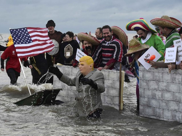 A swimmer dressed as U.S. President-elect Donald Trump, takes part in the New Year's Day swim as other swimmers dressed as Mexicans hold up a wall, at Saundersfoot in Wales, Britain, January 1, 2017. (Photo by Rebecca Naden/Reuters)