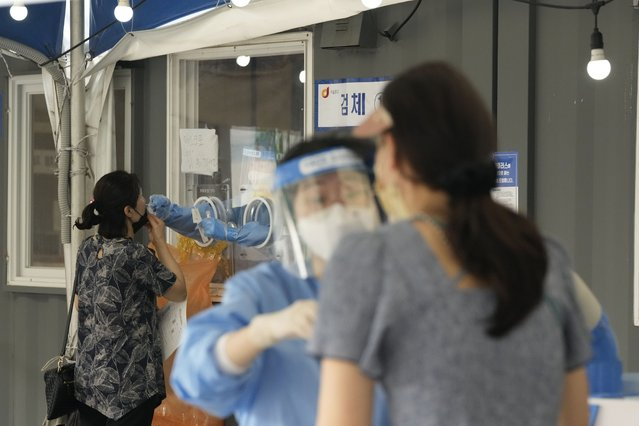 A medical worker in a booth takes a nasal sample from a woman at a makeshift testing site in Seoul, South Korea, Tuesday, July 20, 2021. (Photo by Ahn Young-joon/AP Photo)